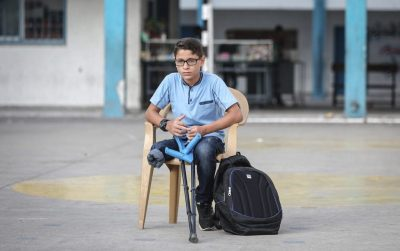World Health Organization photo of a Palestinian youth amputee with crutches. He is wearing glasses, a blue top and jeans.