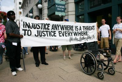 A wheelchairs with Justin Dart's hat on the seat is in front of a sign with a quote from Dr. Martin Luther King Jr.
